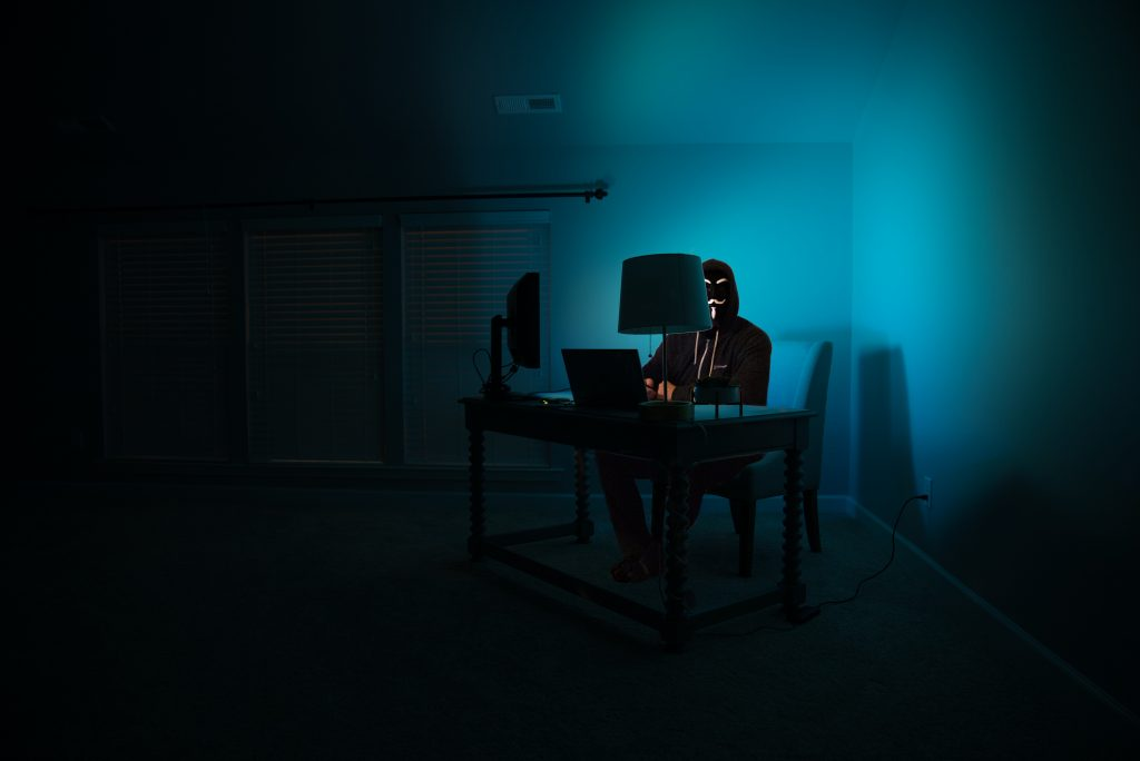 Man wearing a mask in dark room in front of computer