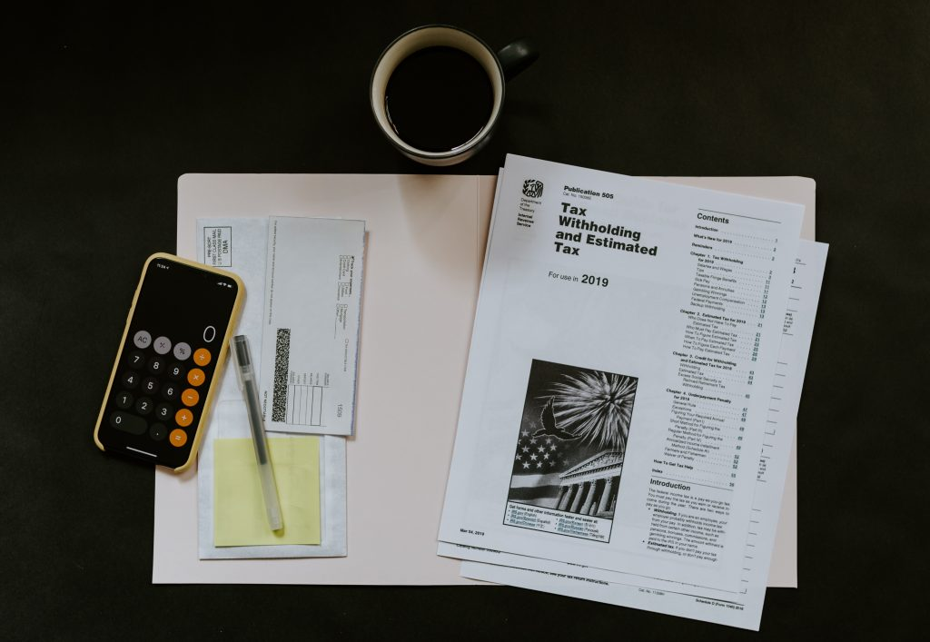 "Open Manilla folder with a calculator, check book and pen on one side, and a stack of paper that says ""Tax Withholding and Estimated Tax"" on the other. A cup of coffee is placed above the folder on a dark background."